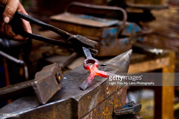blacksmith working on anvil - tongs work tool stock photos and pictures