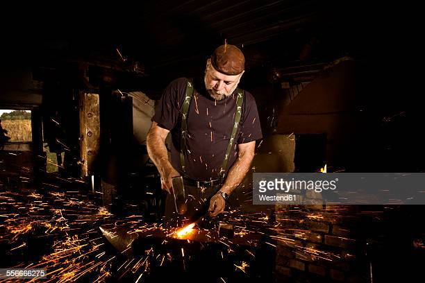 Blacksmith working with hammer at anvil surrounded by sparks