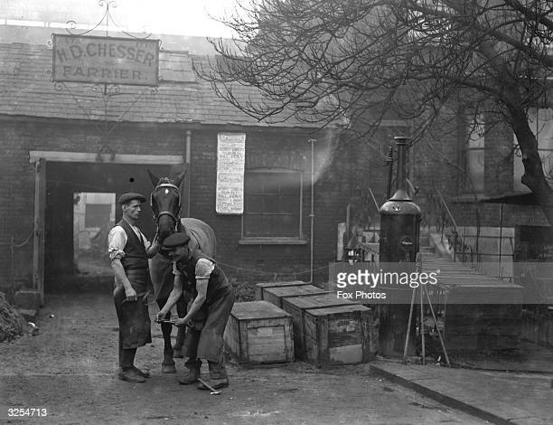 Blacksmiths at work at their smithy which also has a petrol pump at Wood Green
