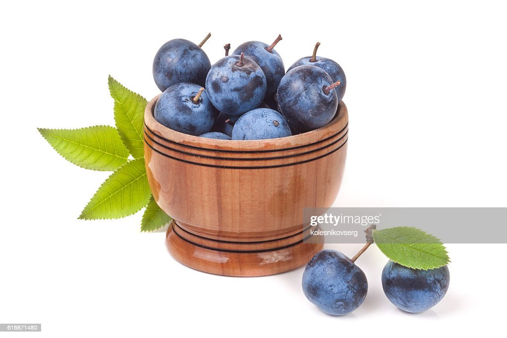 blackthorn berries with leaves in a wooden bowl isolated on : Stock Photo