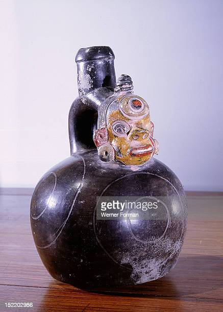 Blackware stirrup spout vessel with trophy head modelled below spout A concentric circle motif on the forehead of the trophy head is repeated on the...