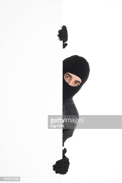black-wearing thief spying out the white wall/background - thief stock pictures, royalty-free photos & images