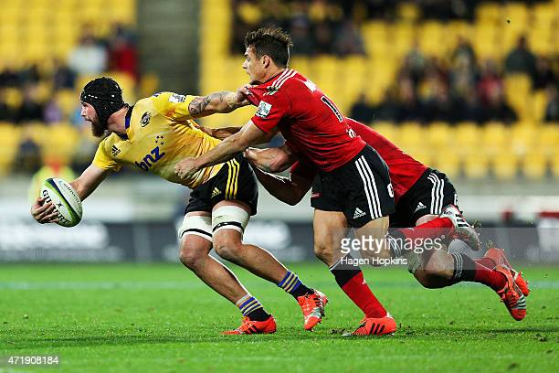 Blade Thomson of the Hurricanes is tackled by Dan Carter of the Crusaders during the round 12 Super Rugby match between the Hurricanes and the...