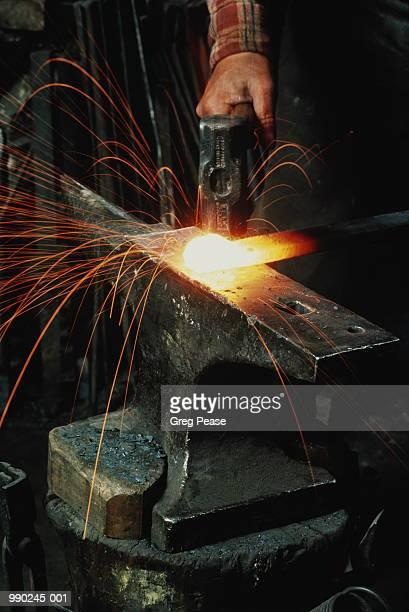 Bladesmith hammering on metal