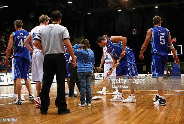 Blagoj Janev of the Spirit helps mop up sweat from the floor during the round 22 NBL match between the Sydney Spirit and the New Zealand Breakers at...