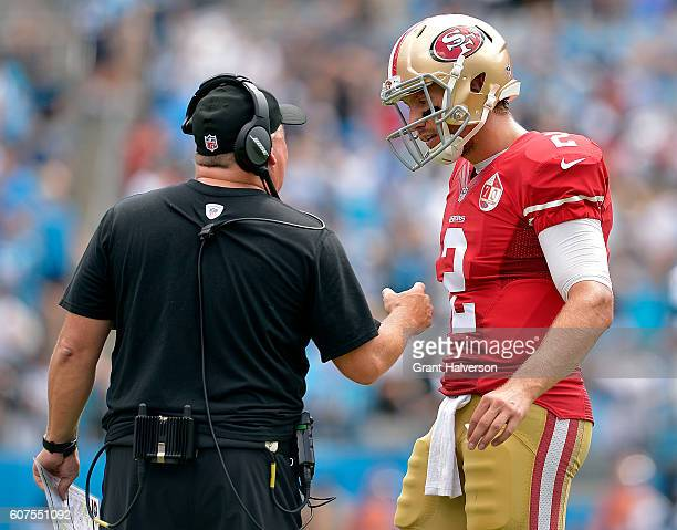 Blaine Gabbert confers with head coach Chip Kelly of the San Francisco 49ers during the game against the Carolina Panthers at Bank of America Stadium...