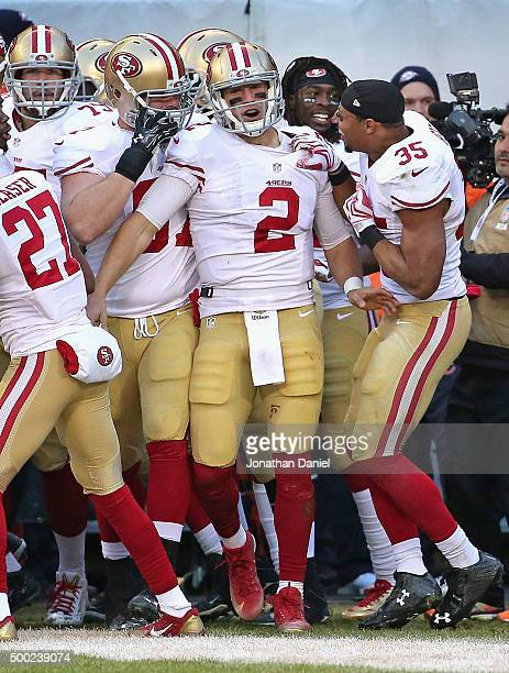 Blaine Gabbert of the San Francisco 49ers is mobbed by teammates after throwing the game winning touchdown pass against the Chicago Bears at Soldier...