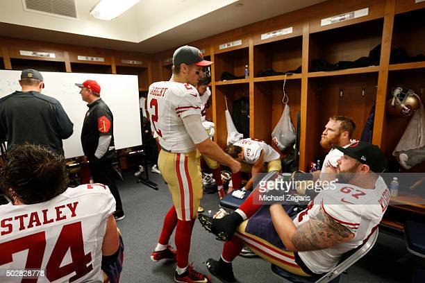 Blaine Gabbert of the San Francisco 49ers talks with Daniel Kilgore and Erik Pears in the locker room during halftime of the game against the Detroit...