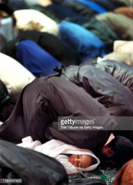 Blaine Mn, Monday 3/5/01 Eid-al-Adha holiday----- Three-year-old Kalif Rabi Mohamed takes a nap as his father to his right Rabi Mahamed Kali and...