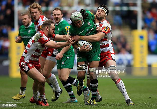 Blair Cowan of London Irish is tackled by Bill Meakes and Jeremy Thrush of Gloucester during the Aviva Premiership match between London Irish and...