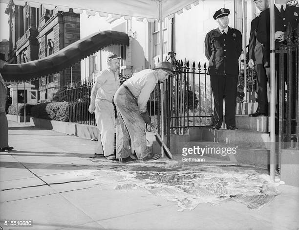 A Blair House employee scrubs blood from the Blair House steps and walk after White House police shot down two gunmen who opened fire on the...