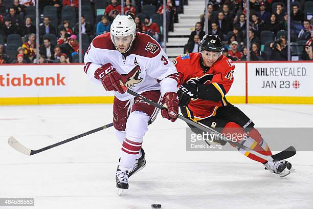 Blair Jones of the Calgary Flames tries to check Keith Yandle of the Phoenix Coyotes during an NHL game at Scotiabank Saddledome on January 22 2014...