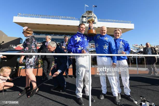 Blair Orange driving Cruz Bromac and trainers Mark Purdon and Natalie Rasmussen pose with the New Zealand Cup and the trophies for the best driver...