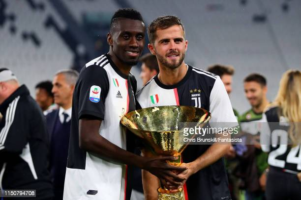 Blaise Matuidi and Miralem Pjanic of Juventus pose with the Serie A trophy alongside his family following the Serie A match between Juventus and...