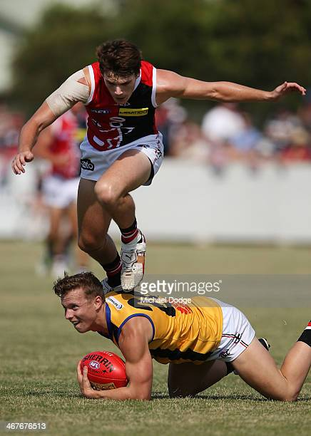 Blake Acres jumps over Dalton Graham during a St Kilda Saints AFL intraclub match at Linen House Oval on February 8 2014 in Melbourne Australia