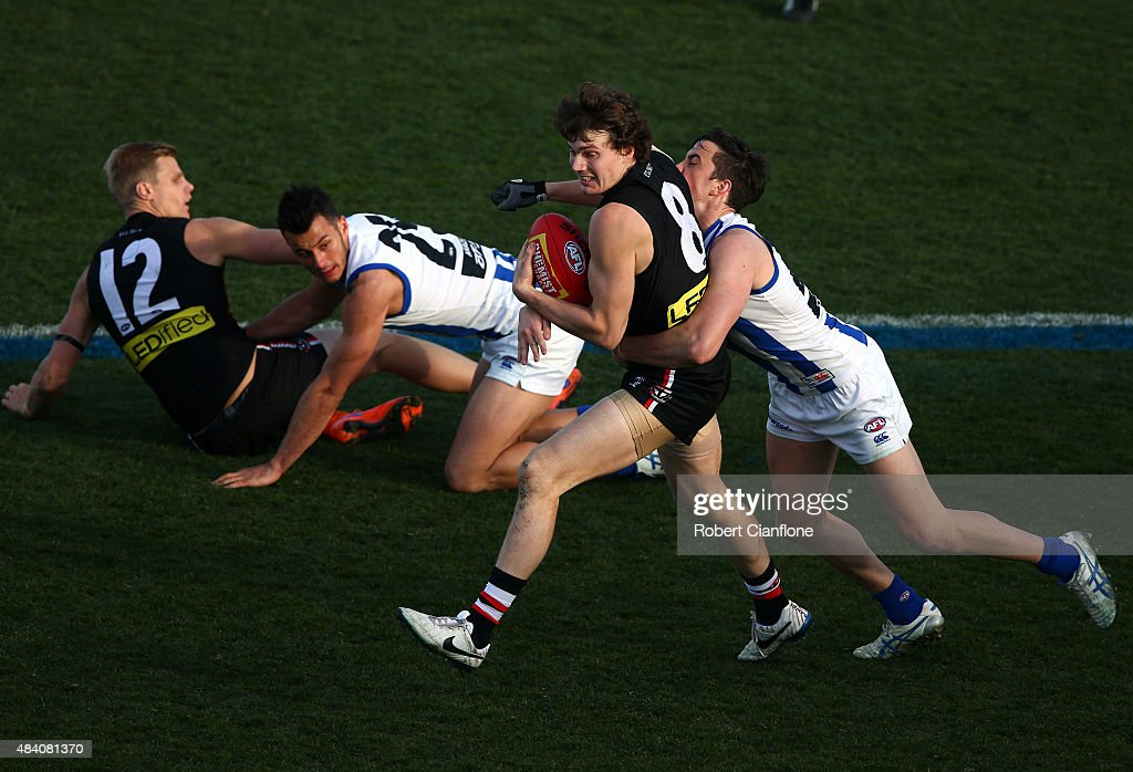 Blake Acres of the Saints is challenged by Taylor Garner of the Kangaroos during the round 20 AFL match between the North Melbourne Kangaroos and the St Kilda Saints at Blundstone Arena on August 15, 2015 in Hobart, Australia.
