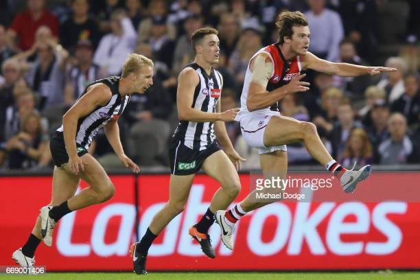 Blake Acres of the Saints kicks the ball away from Josh Smith and Tim Broomhead of the Magpies during the round four AFL match between the...