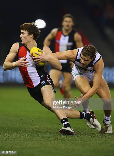 Blake Acres of the Saints runs with the ball away from Jake Kolodjashnij of the Cats during the round 14 AFL match between the St Kilda Saints and...