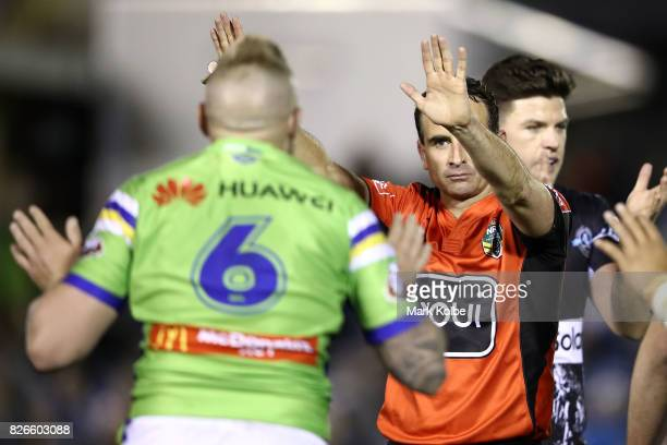Blake Austin of the Raiders appeals to referee Gerard Sutton as he sin bins Josh Papalii during the round 22 NRL match between the Cronulla Sharks...