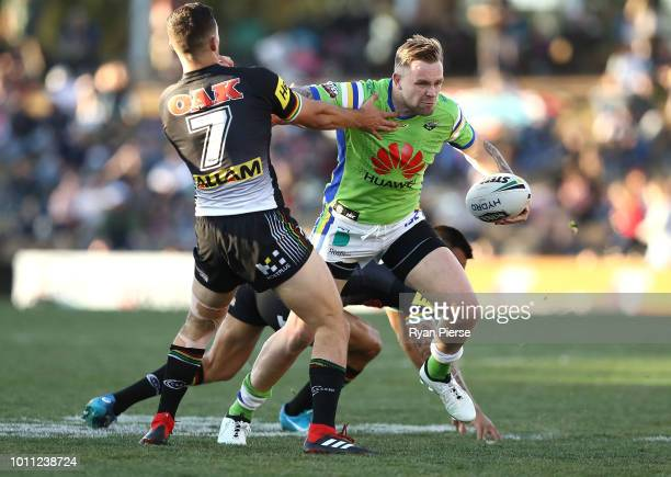 Blake Austin of the Raiders is tackled by Nathan Cleary of the Panthers during the round 21 NRL match between the Penrith Panthers and the Canberra...