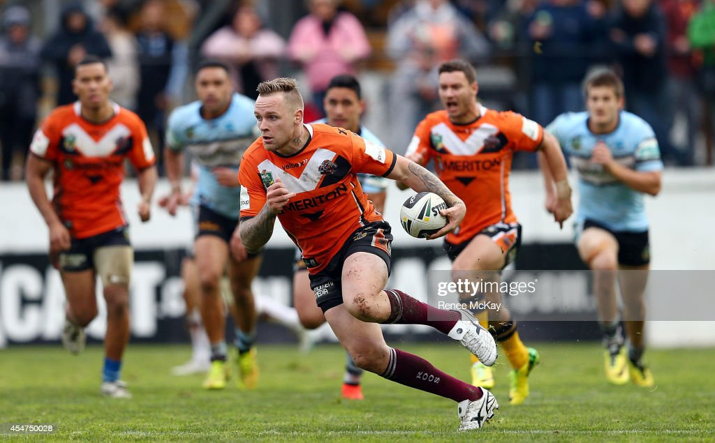 Blake Austin of the Tigers makes a break during the round 26 NRL match between the Wests Tigers and the Cronulla Sharks at Leichhardt Oval on September 6, 2014 in Sydney, Australia.