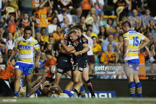 Blake Ayshford of the Tigers celebrates with team mates after scoring a try during the round three NRL match between the Wests Tigers and the...