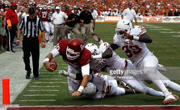 Blake Bell of the Oklahoma Sooners dives into the endzone to score against Mykkele Thompson of the Texas Longhorns Demarco Cobbs of the Texas...