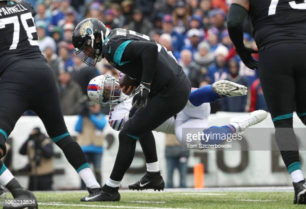 Blake Bortles of the Jacksonville Jaguars evades an attempted sack by Jerry Hughes of the Buffalo Bills in the first quarter during NFL game action...