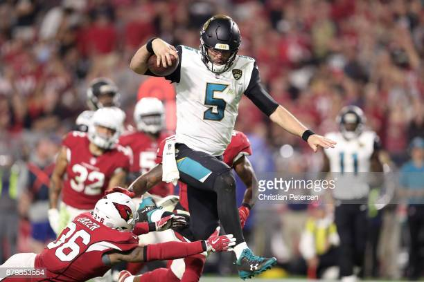 Blake Bortles of the Jacksonville Jaguars jumps to avoid a tackle by Budda Baker of the Arizona Cardinals to rush in a 17 yard touchdown in the...