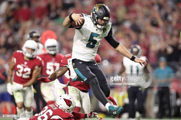 Blake Bortles of the Jacksonville Jaguars jumps to avoid a tackle by Budda Baker of the Arizona Cardinals in the second half at University of Phoenix...
