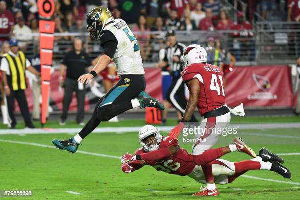 Blake Bortles of the Jacksonville Jaguars jumps to avoid a tackle by Budda Baker of the Arizona Cardinals and rushes in a 17 yard touchdown in the...