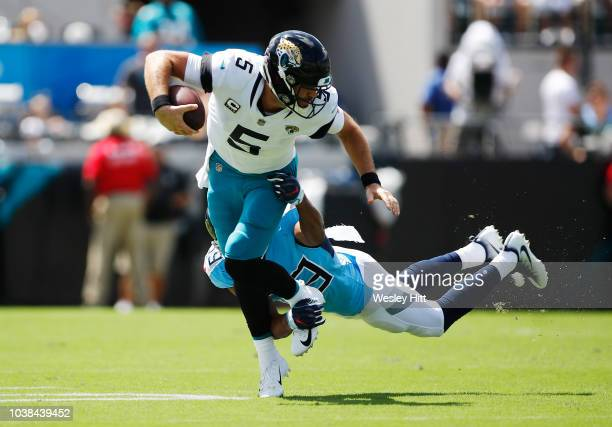Blake Bortles of the Jacksonville Jaguars runs away from the tackle of Wesley Woodyard of the Tennessee Titans during their game at TIAA Bank Field...