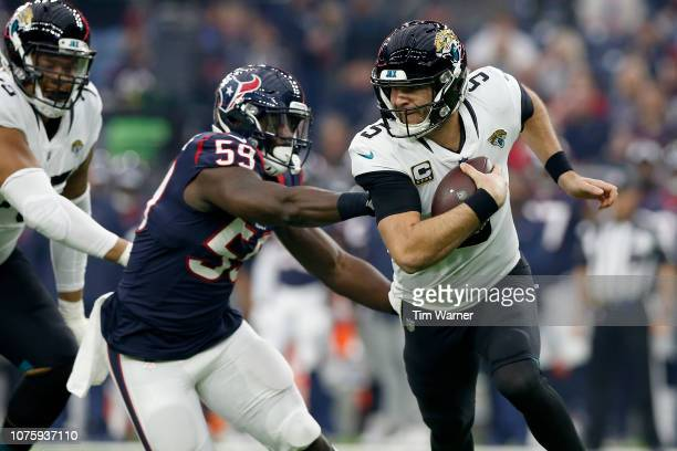 Blake Bortles of the Jacksonville Jaguars scrambles out of the pocket under pressure by Whitney Mercilus of the Houston Texans in the first quarter...