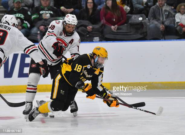 Blake Christensen of the American International Yellow Jackets is tripped by Jon Lizotte of the St Cloud State Huskies during an NCAA Division I...