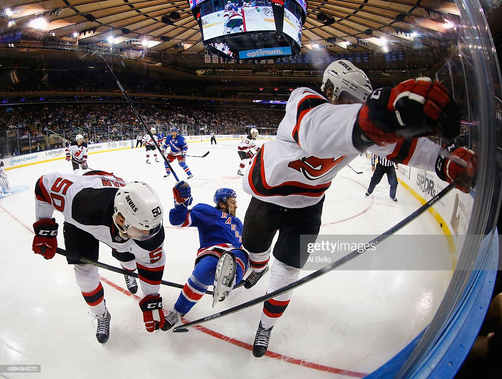Blake Coleman #50 and Adam Larsson #5 of the New Jersey Devils check Raphael Diaz #46 of the New York Rangers during their Pre Season game at Madison Square Garden on September 21, 2015 in New York City.