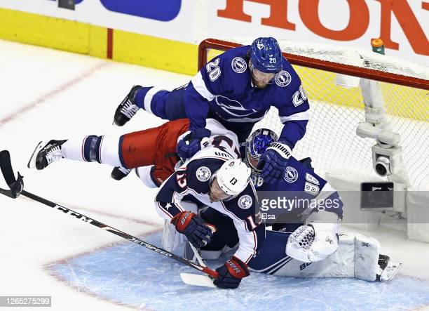 Blake Coleman and Andrei Vasilevskiy of the Tampa Bay Lightning defend against Cam Atkinson of the Columbus Blue Jackets during the first period in...