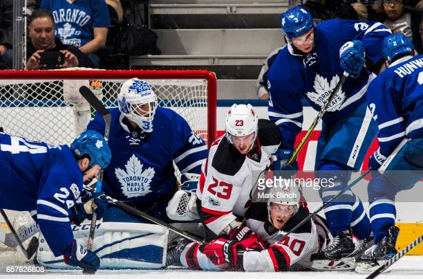 Blake Coleman and Stefan Noesen of the New Jersey Devils battles with Curtis McElhinney Brian Boyle Alexey Marchenko of the Toronto Maple Leafs...