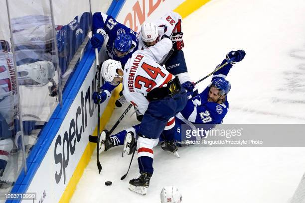 Blake Coleman and Yanni Gourde of the Tampa Bay Lightning battles for the puck with Jonas Siegenthaler and Radko Gudas of the Washington Capitals...