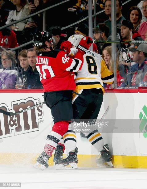 Blake Coleman of the New Jersey Devils and Brian Dumoulin of the Pittsburgh Penguins come together at the boards during the game at Prudential Center...