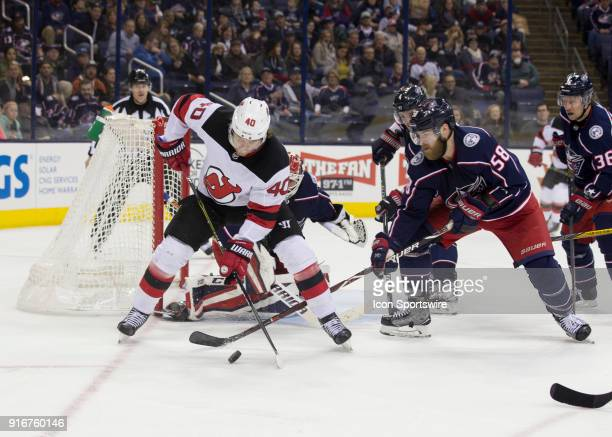 Blake Coleman of the New Jersey Devils and David Savard of the Columbus Blue Jackets battle for the loose puck during the third period of the game...