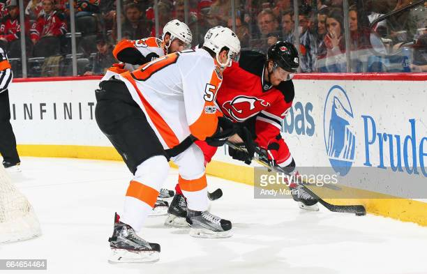 Blake Coleman of the New Jersey Devils and Samuel Morin of the Philadelphia Flyers playing in his first NHL game battle for a loose puck at...