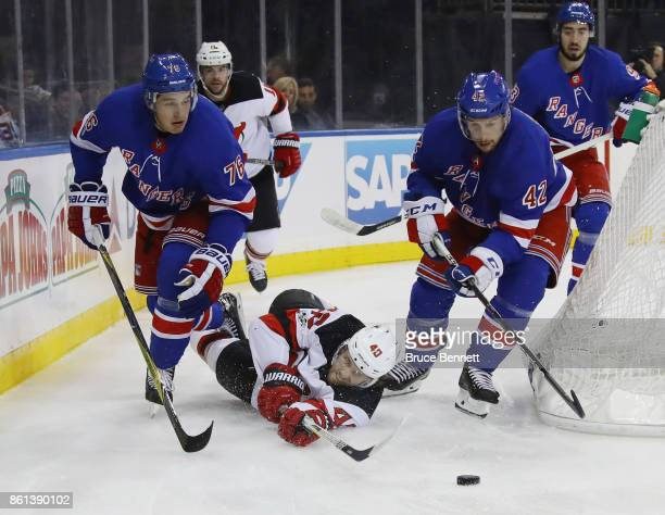 Blake Coleman of the New Jersey Devils attempts to get the puck away from Brady Skjei and Brendan Smith of the New York Rangers at Madison Square...