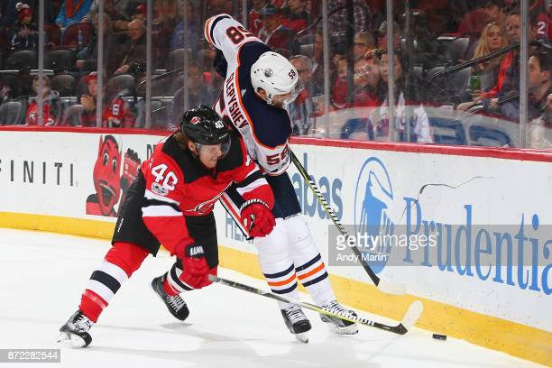 Blake Coleman of the New Jersey Devils battles for the puck against Anton Slepyshev of the Edmonton Oilers during the game at Prudential Center on...