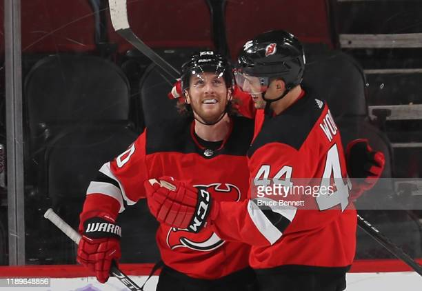 Blake Coleman of the New Jersey Devils celebrates his empty net goal at 19:48 of the third period against the Detroit Red Wings and is joined by...