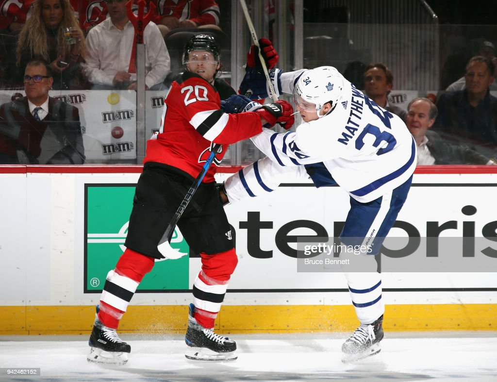 Blake Coleman #20 of the New Jersey Devils checks Auston Matthews #34 of the Toronto Maple Leafs during the third period at the Prudential Center on April 5, 2018 in Newark, New Jersey. The Devils defeated the Leafs 2-1 and clinched a playoff berth in the 2018 Stanley Cup Playoffs.