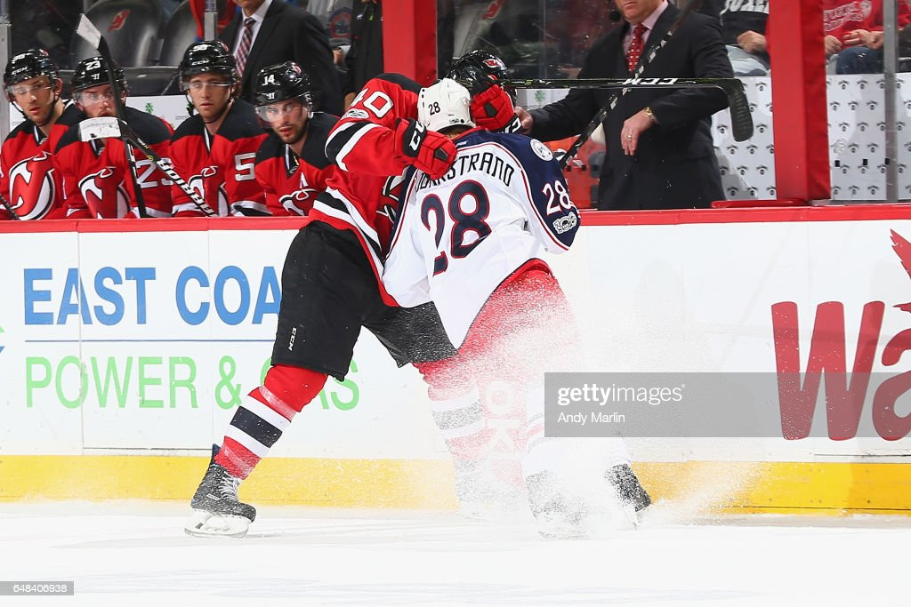 Blake Coleman #40 of the New Jersey Devils gets tangled up with Oliver Bjokrstrand of the Columbus Blue Jackets during the game at Prudential Center on March 5, 2017 in Newark, New Jersey. The Blue Jackets defeated the Devils 3-0.