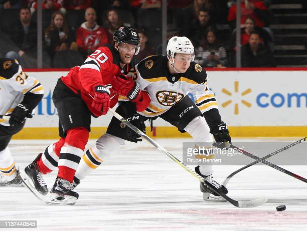 Blake Coleman of the New Jersey Devils holds on to Charlie McAvoy of the Boston Bruins during the first period at the Prudential Center on March 21,...