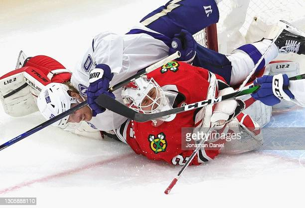Blake Coleman of the Tampa Bay Lightning falls over Kevin Lankinen of the Chicago Blackhawks after taking a shot at the United Center on March 07,...