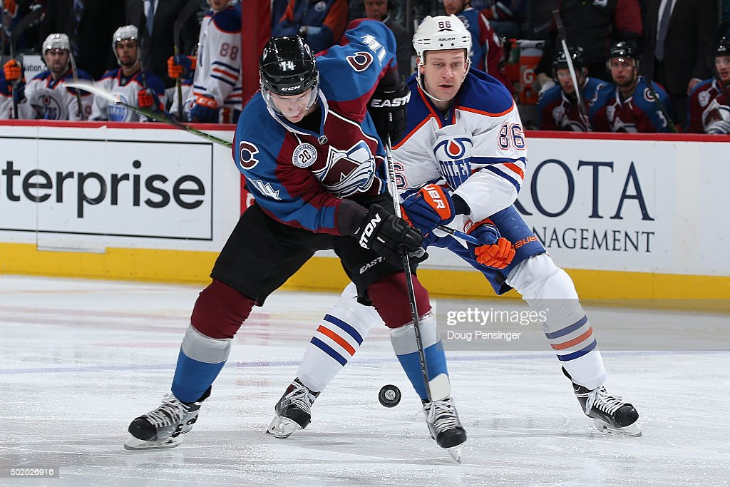 Blake Comeau #14 of the Colorado Avalanche tries to control the puck against Nikita Nikitin #86 of the Edmonton Oilers at Pepsi Center on December 19, 2015 in Denver, Colorado.