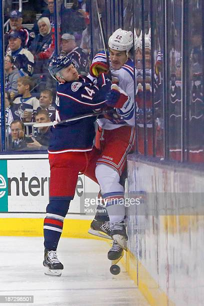 Blake Comeau of the Columbus Blue Jackets checks Brian Boyle of the New York Rangers into the boards while battling for control of the puck during...